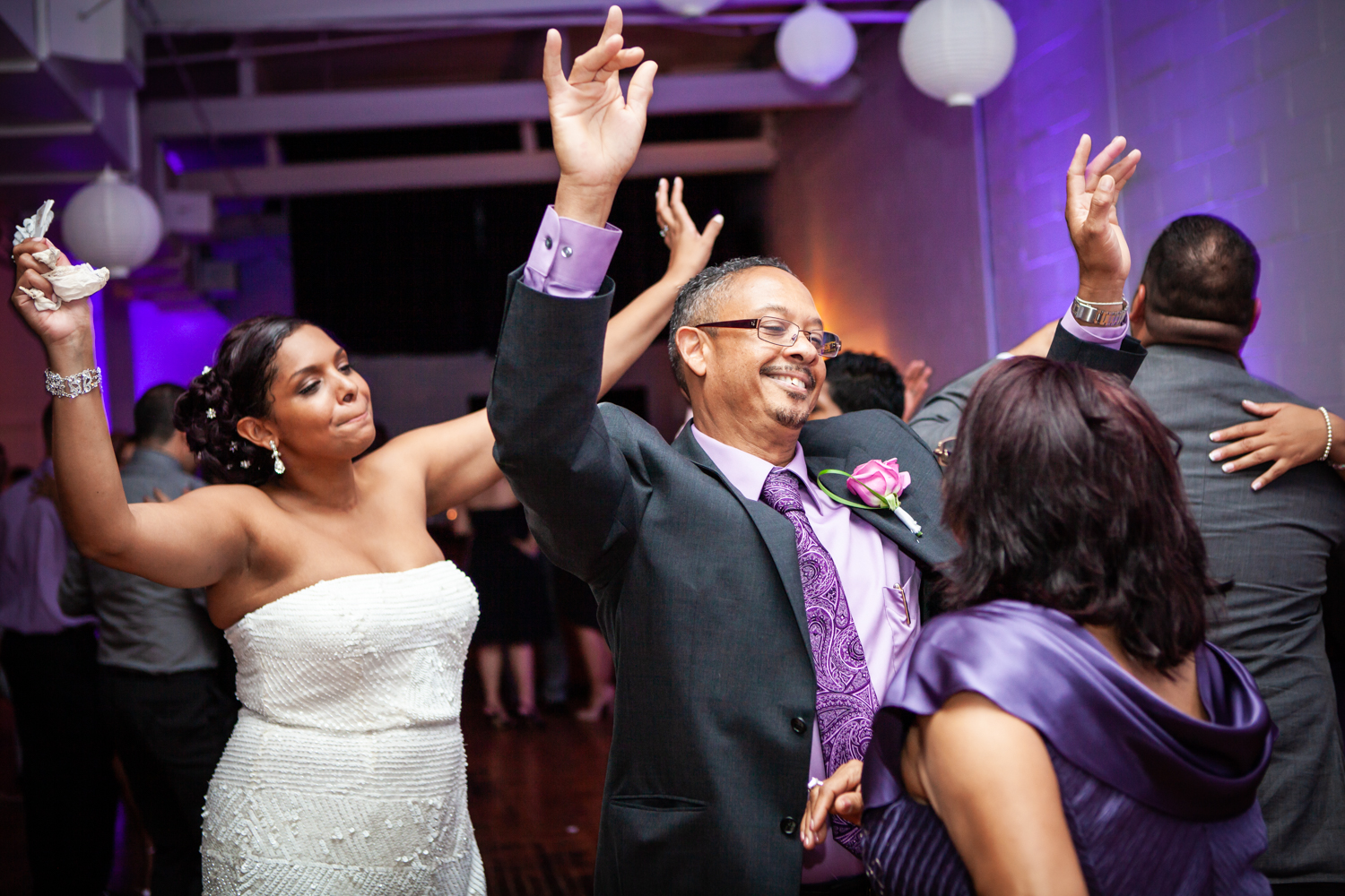 Man dancing in between two women at a wedding reception