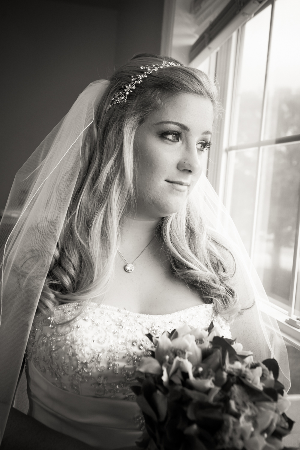 Black and white portrait of bride at window