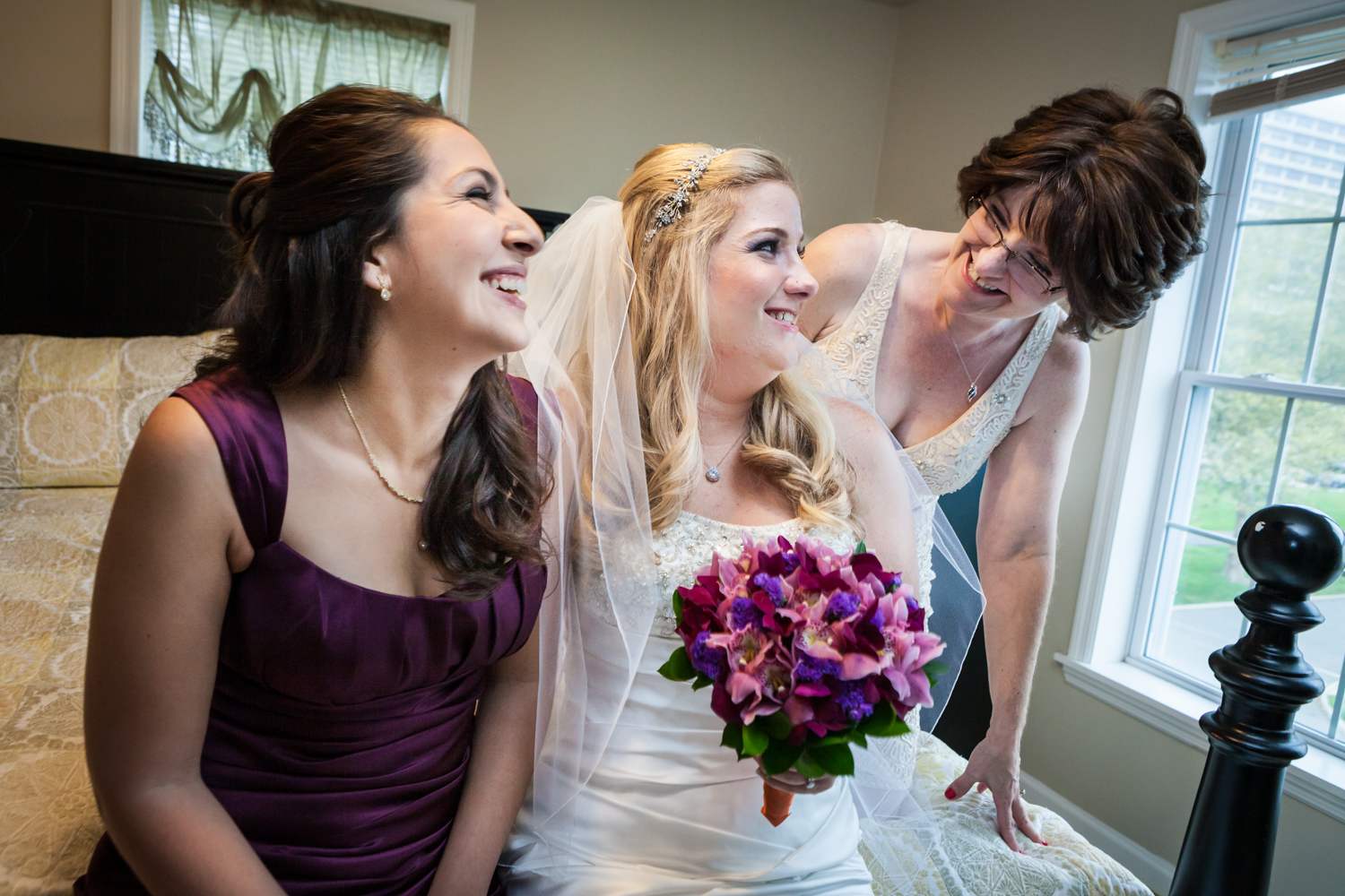 Bride laughing with mother and sister before wedding