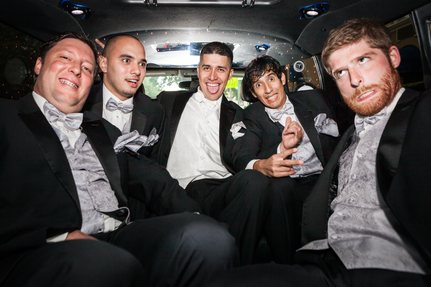 Groom and groomsmen making funny faces in the back of a limo