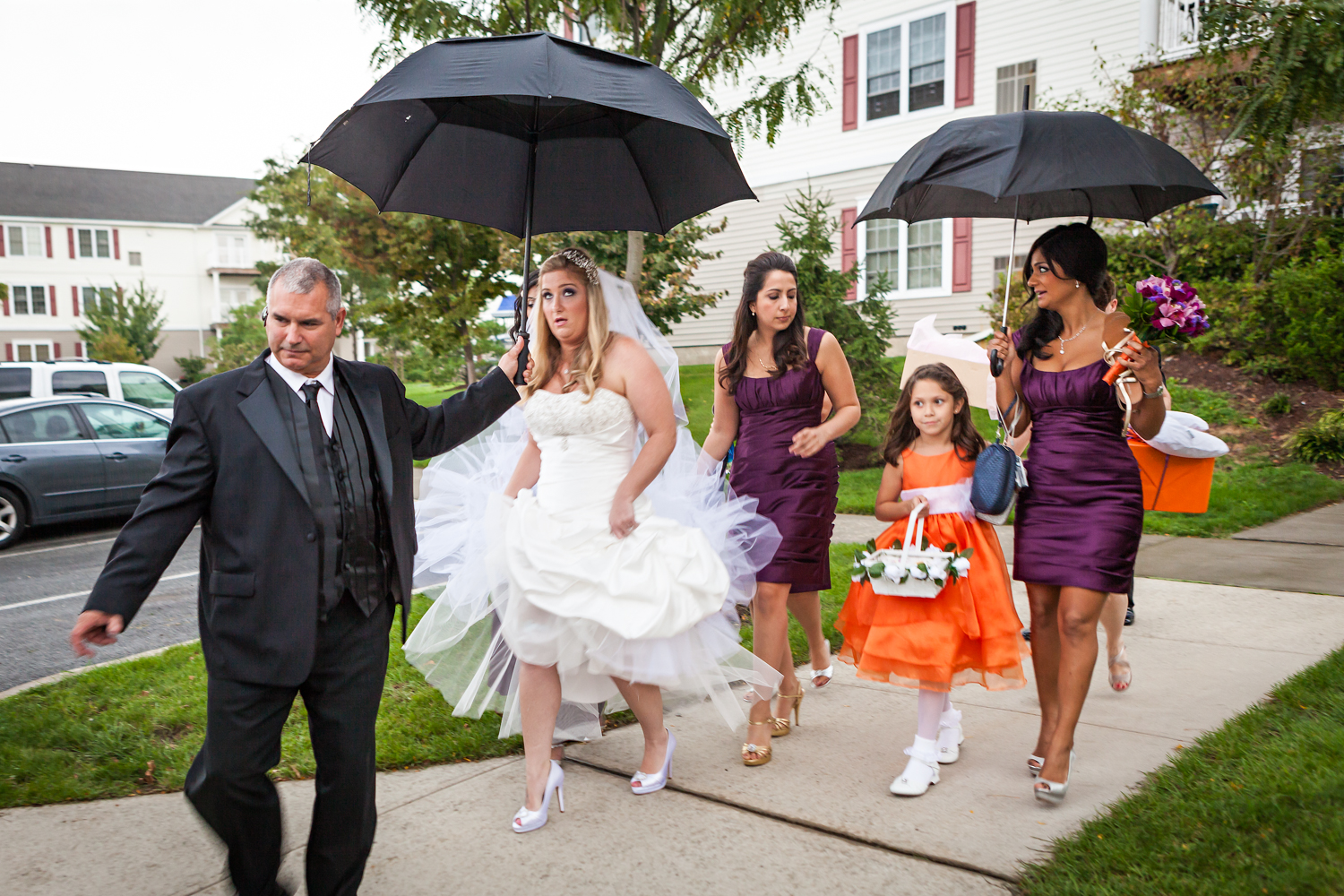 Bride and bridal party walking under umbrellas