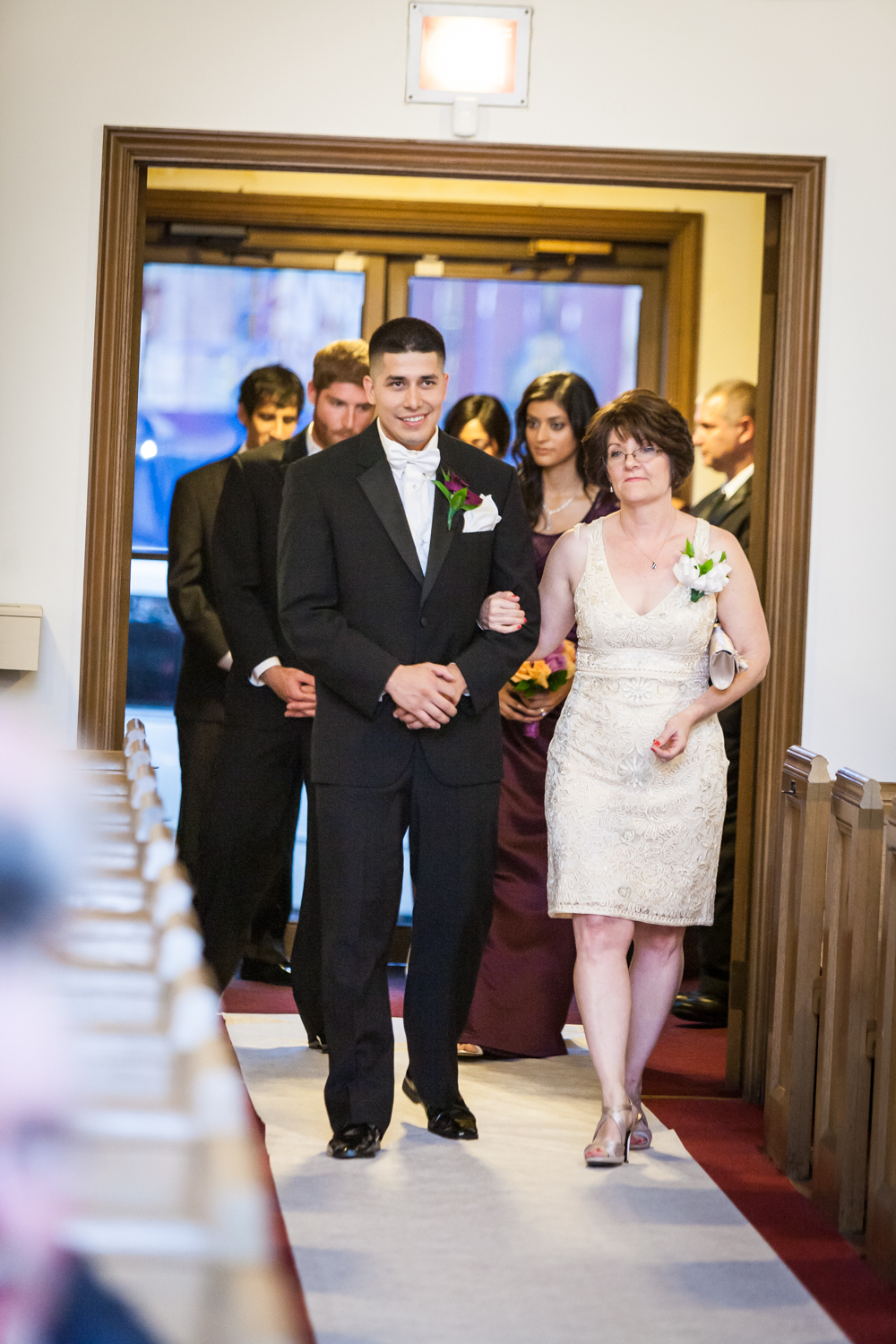 Groom and mother walking down aisle of church at a Fort Hamilton Community Center wedding