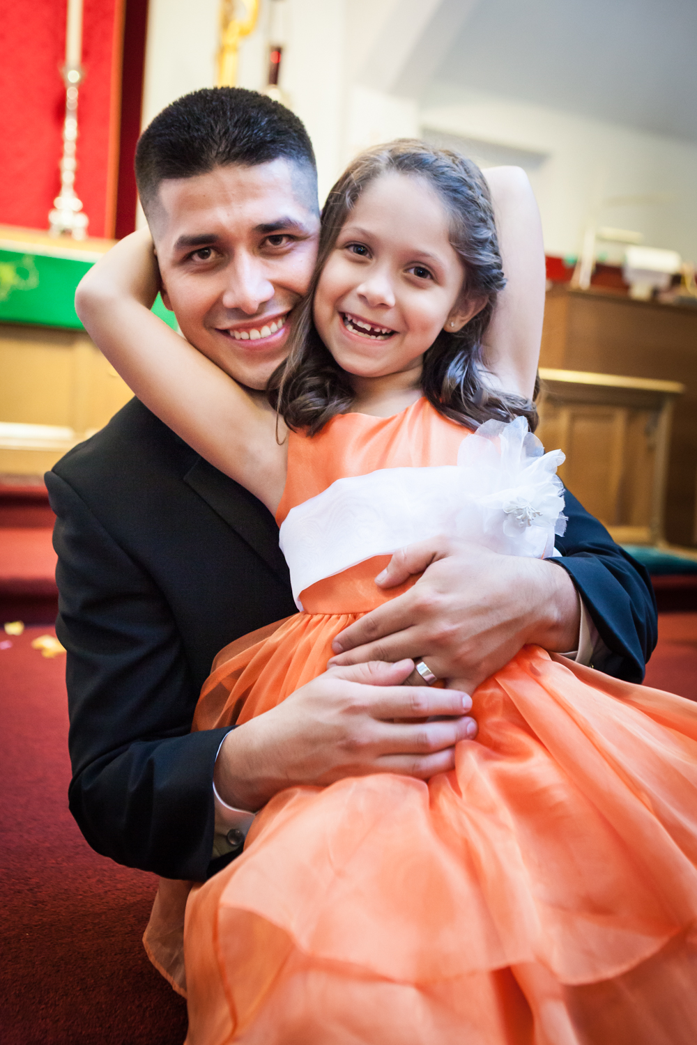 Groom  and little girl wearing orange dress smiling