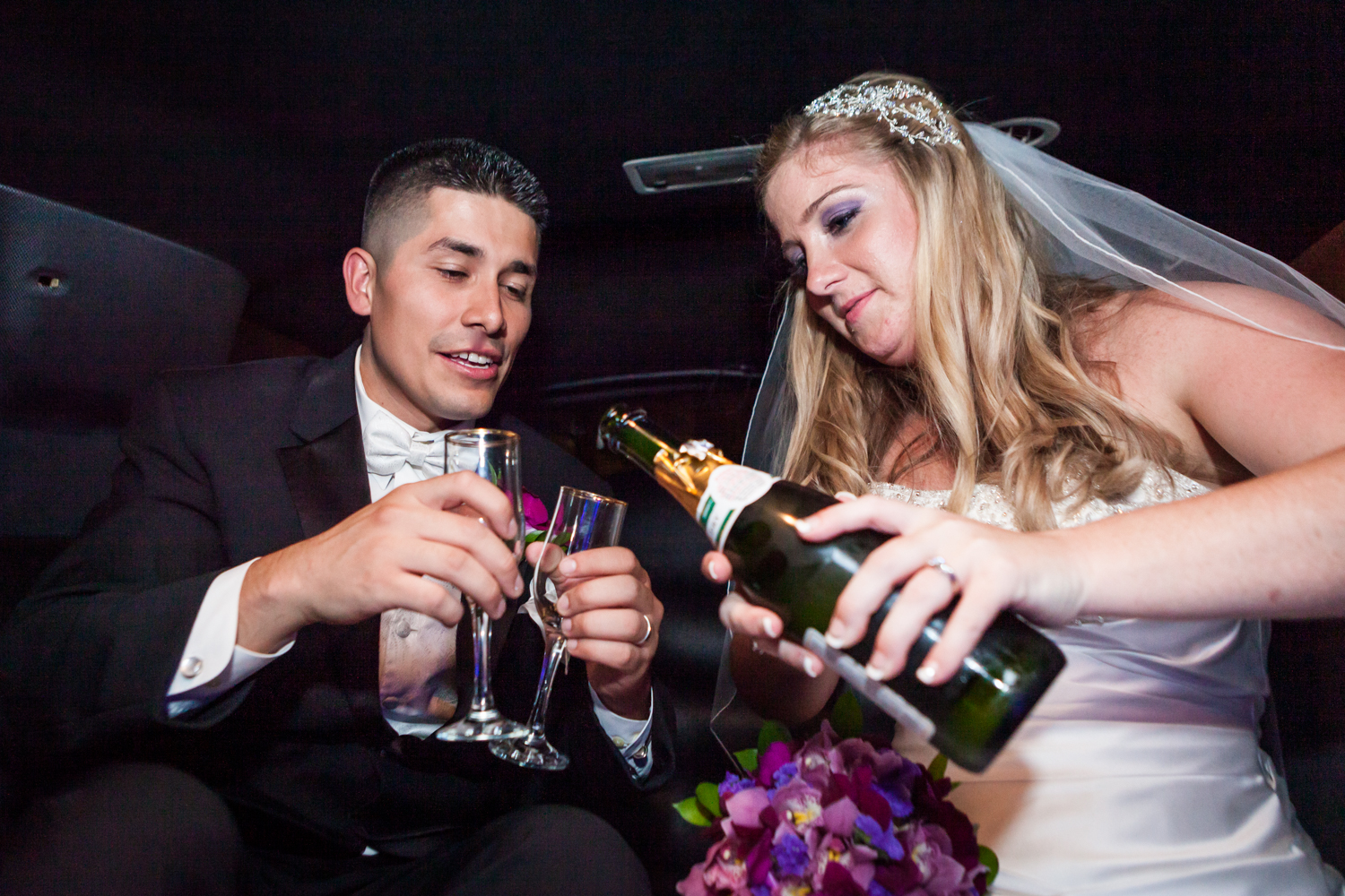 Bride pouring champagne into glasses held by groom