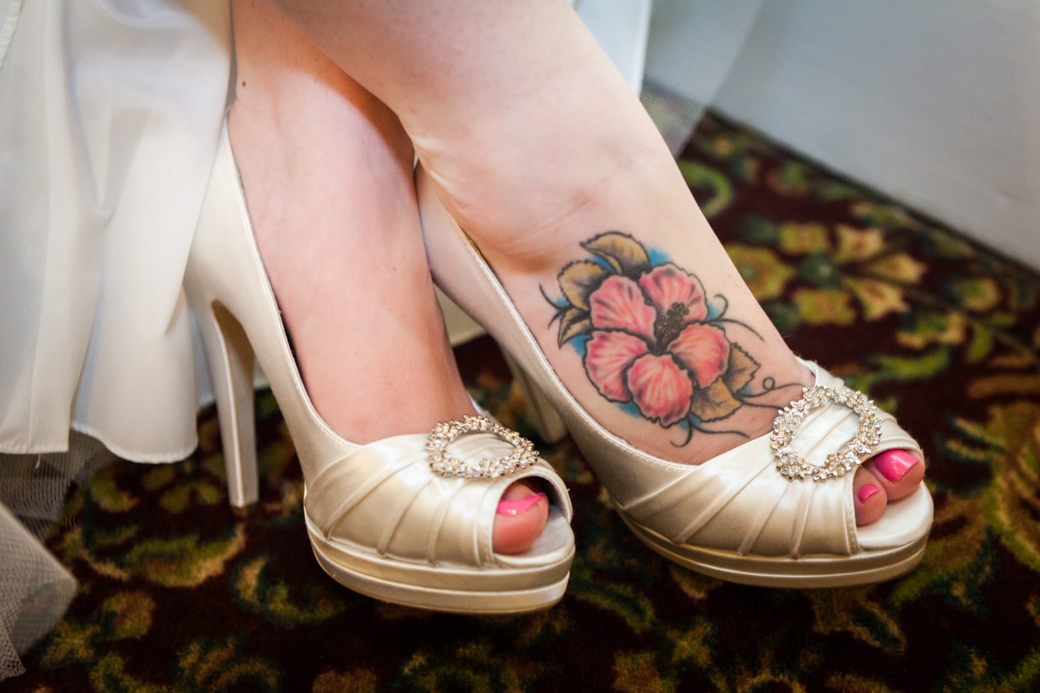 Close up on bride's feet with flower tattoo and satin high heels