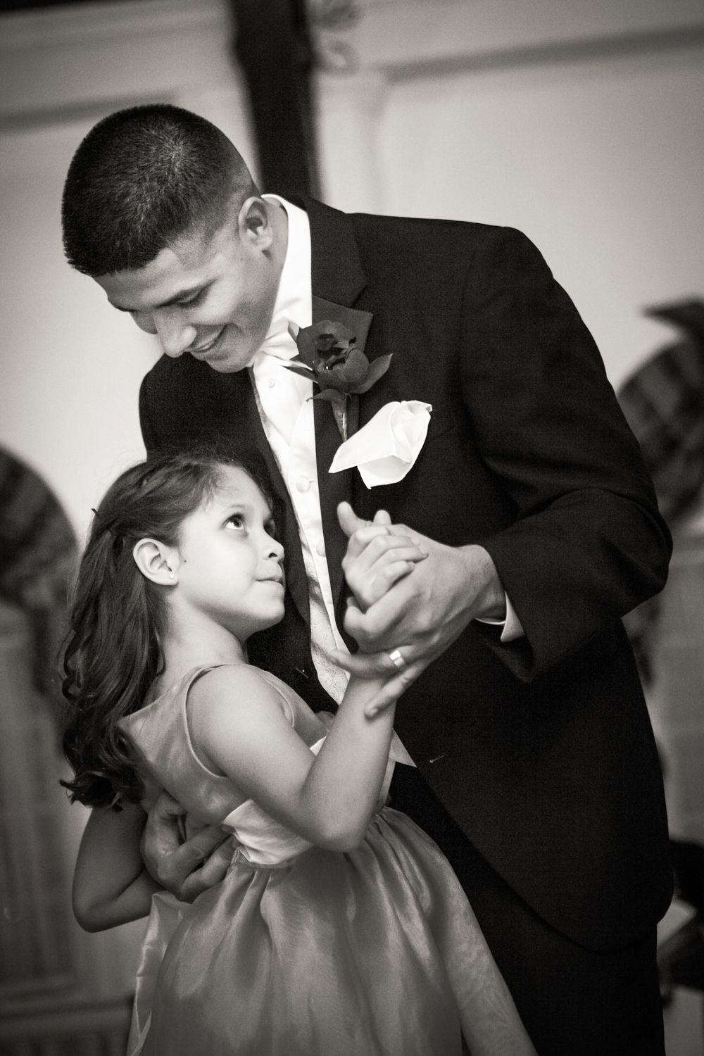 Black and white photo of groom dancing with little girl at a Fort Hamilton Community Center wedding