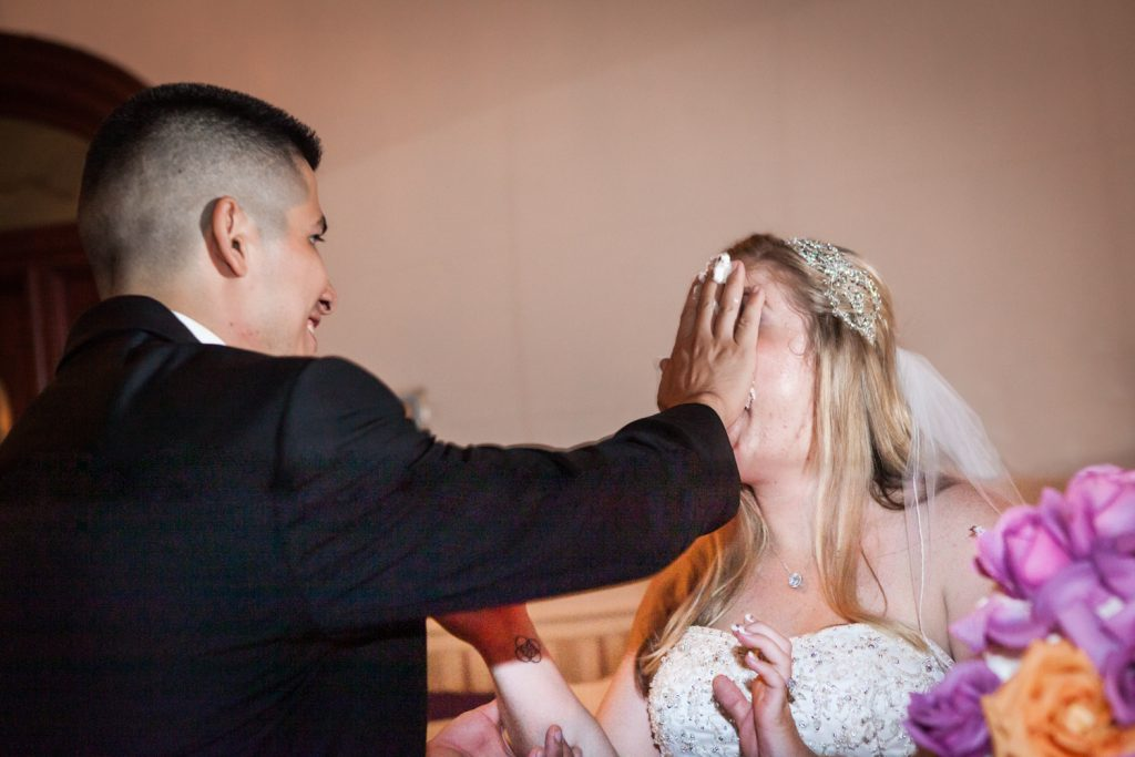 Groom smashing cake into bride's face at a Fort Hamilton Community Center wedding