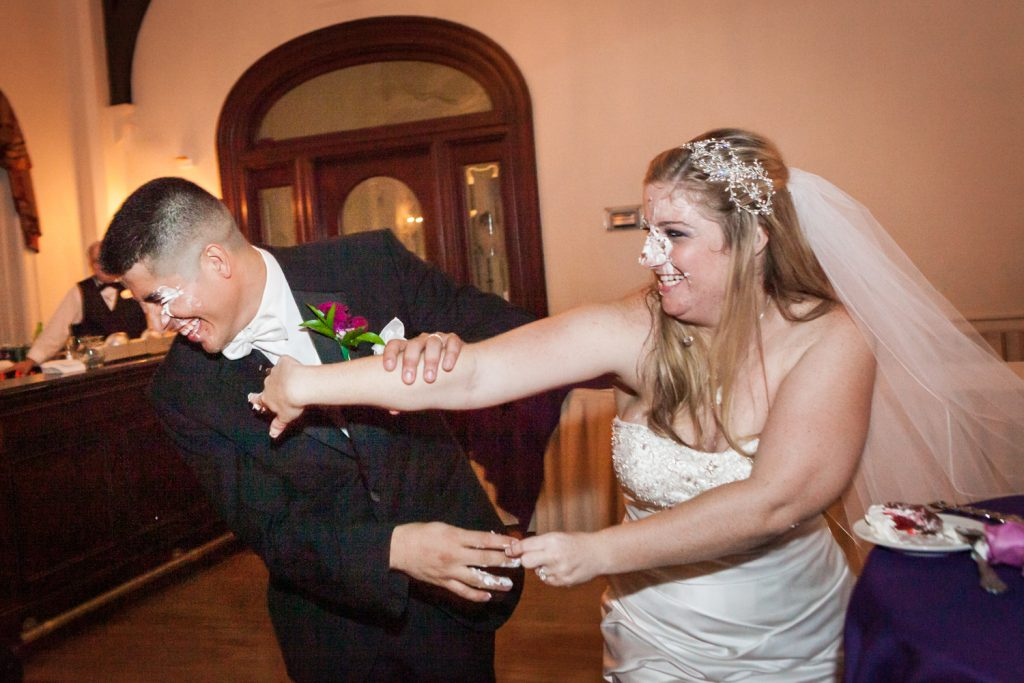 Bride smashing cake into groom's face at a Fort Hamilton Community Center wedding