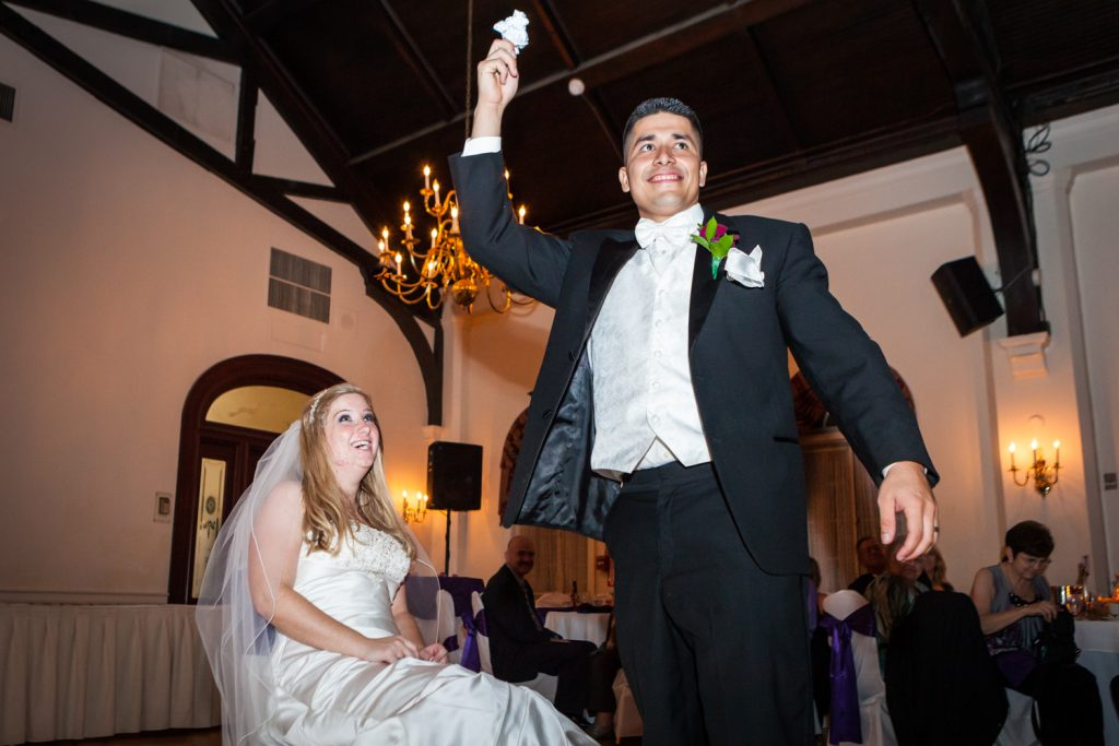 Groom holding up garter at a Fort Hamilton Community Center wedding