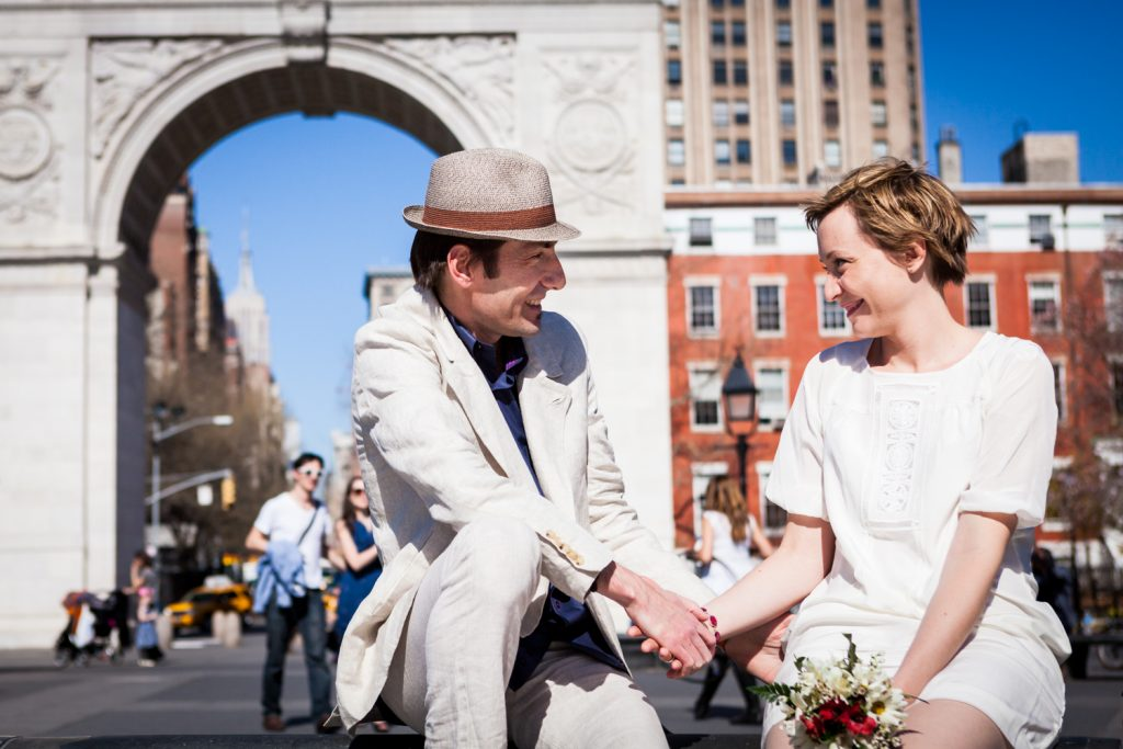 Man and woman holding hands with Washington Square Park arch in background