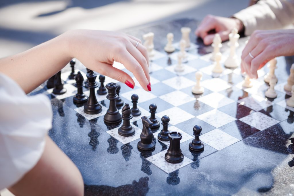 Close up on woman's hand hovering above chess board