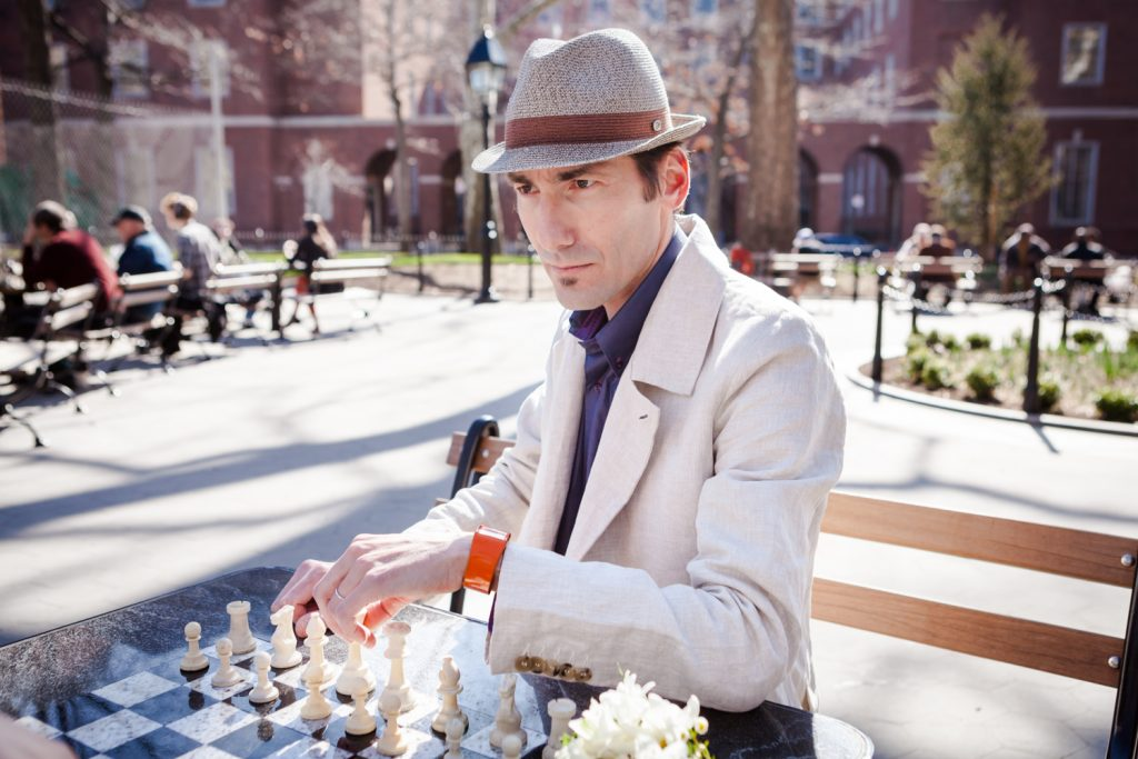 Washington Square Park portrait of man staring intently while playing chess