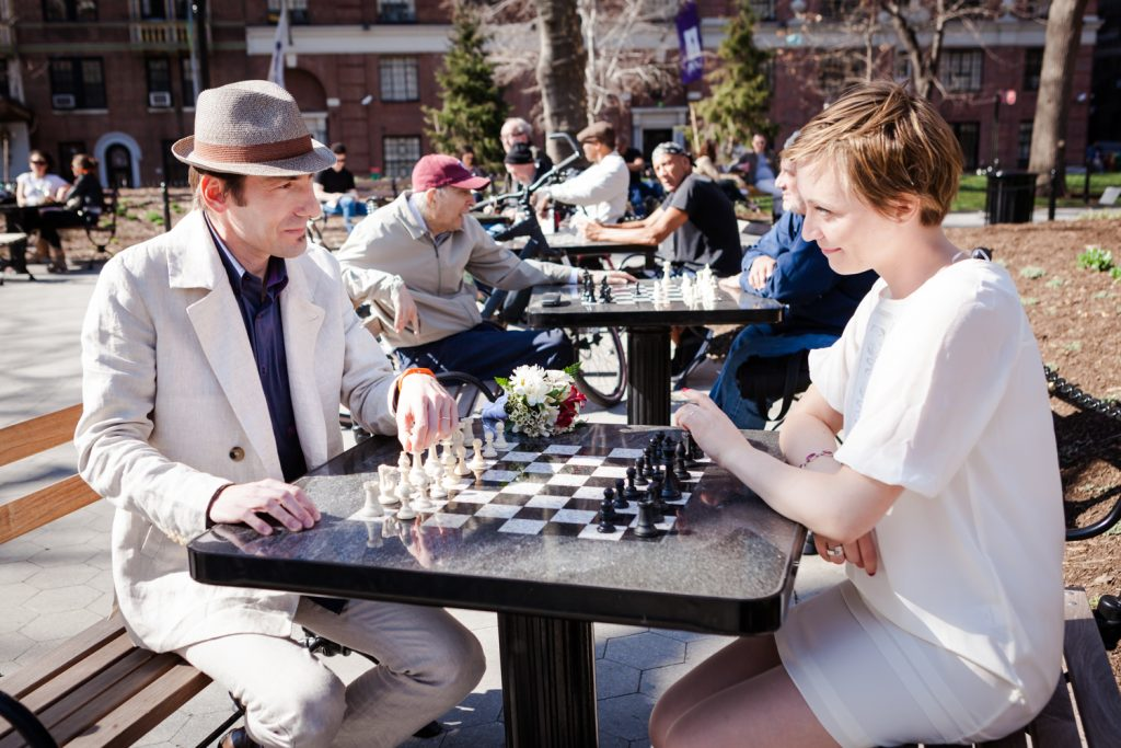 Couple playing chess with other players in the background
