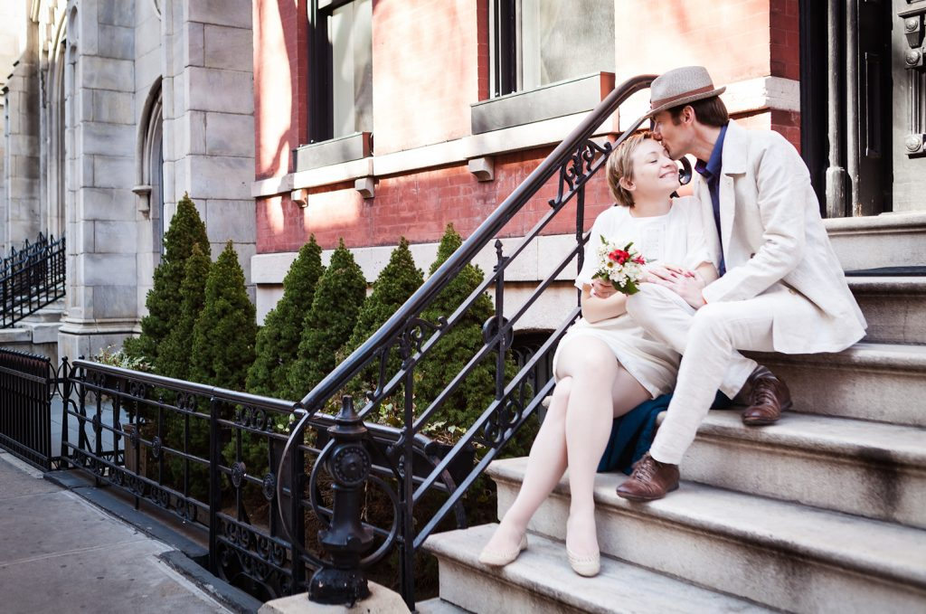 Man kissing woman on side of head while sitting on steps