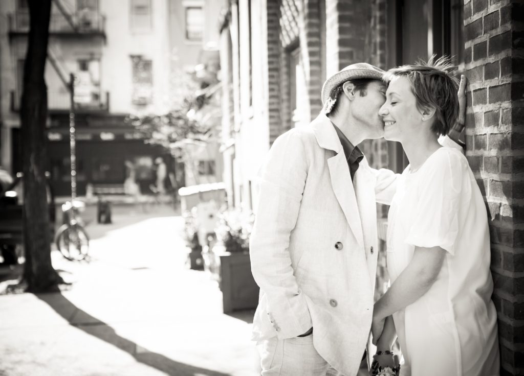 Black and white photo of man kissing woman against brick wall