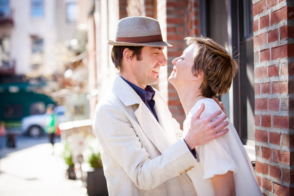 Man and woman laughing against brick wall in Greenwich Village
