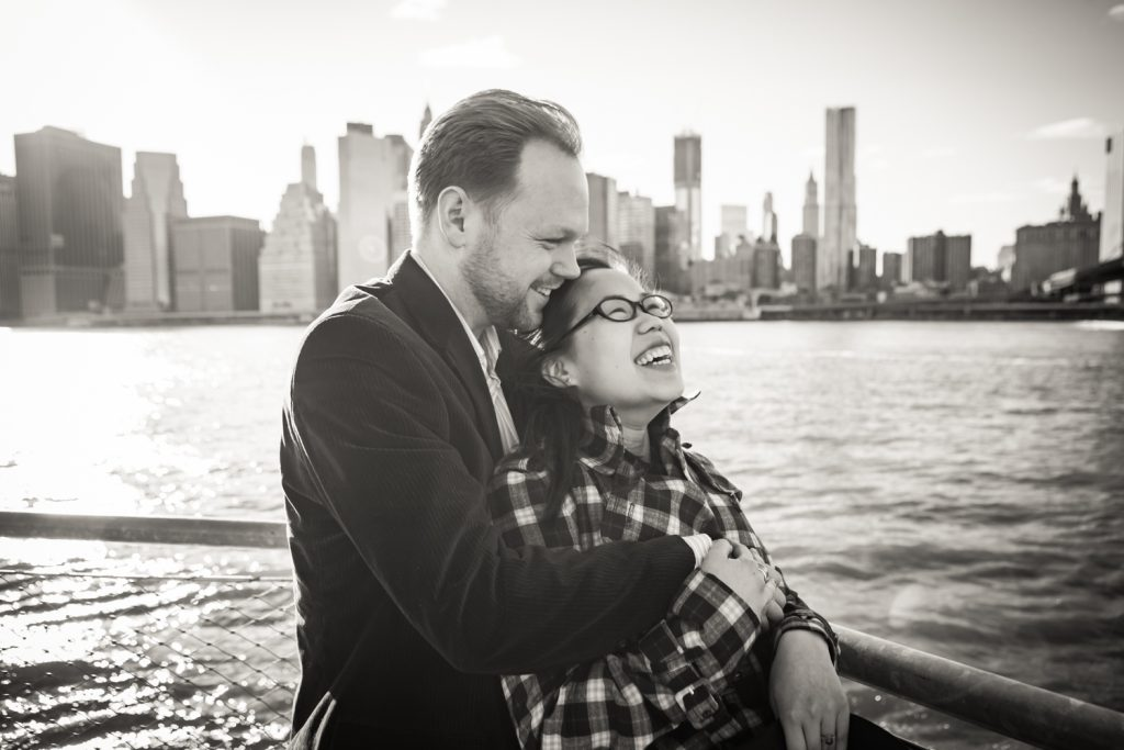 Black and white photo of couple in front of East River with NYC skyline in background