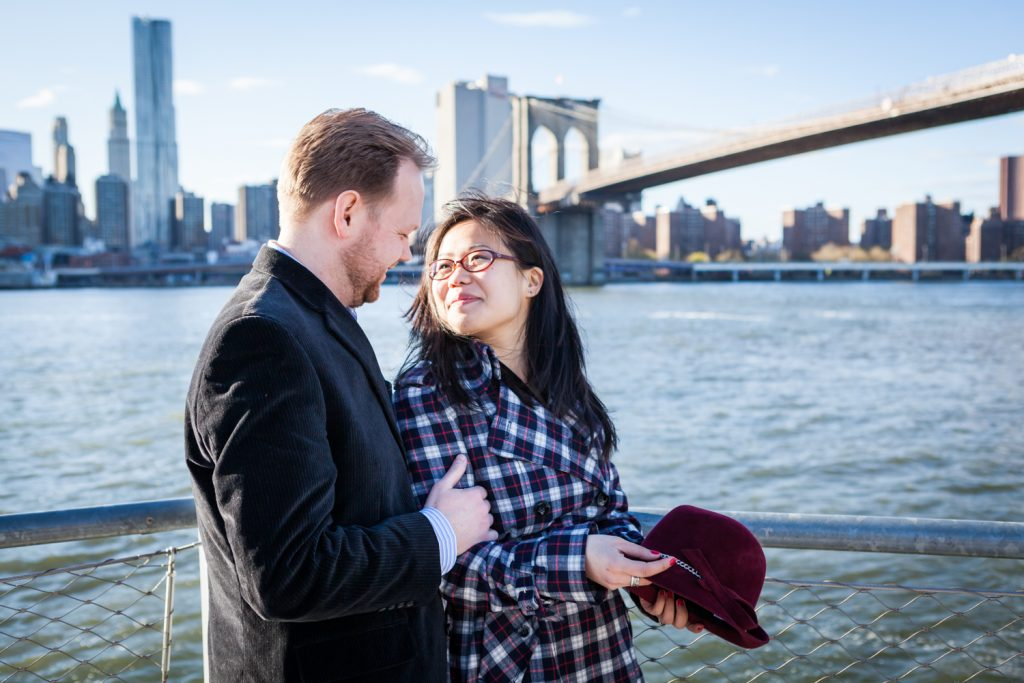 Couple in front of East River with Brooklyn Bridge in background