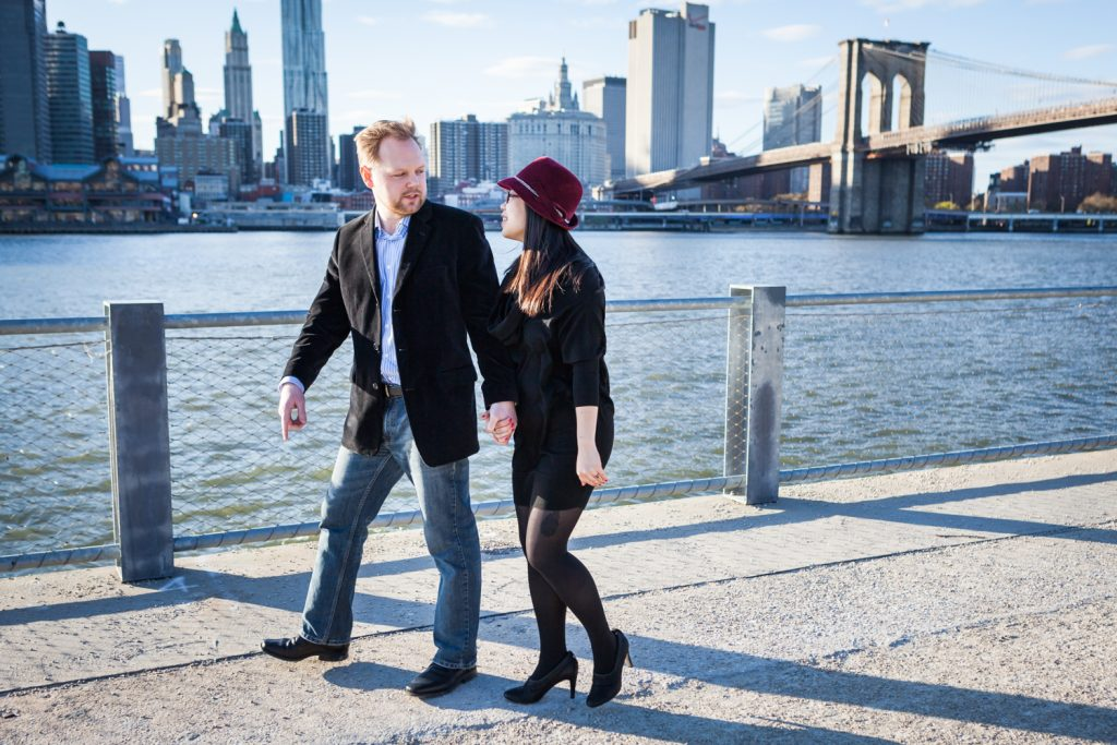 Couple walking in front of East River with Brooklyn Bridge in background