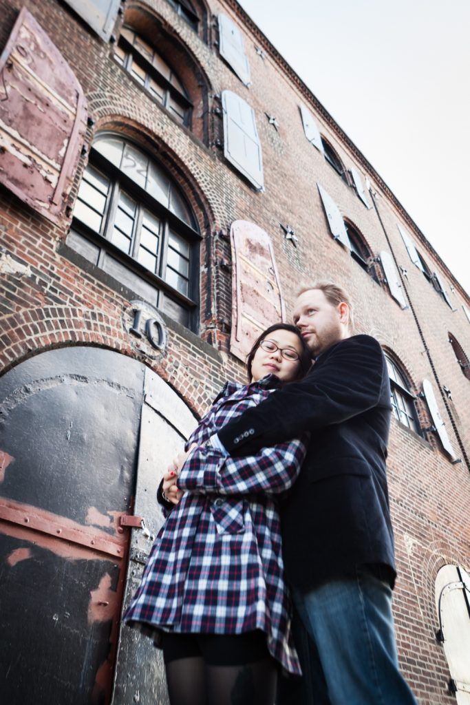 Red Hook engagement photos of couple against brick building