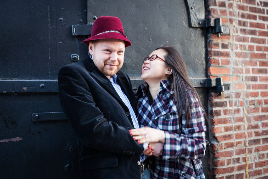 Red Hook engagement photos of couple making funny faces in front of black door