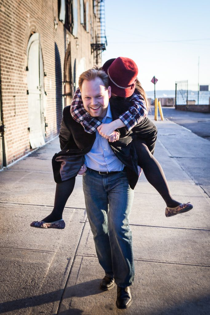Red Hook engagement photos of man giving woman a piggyback ride