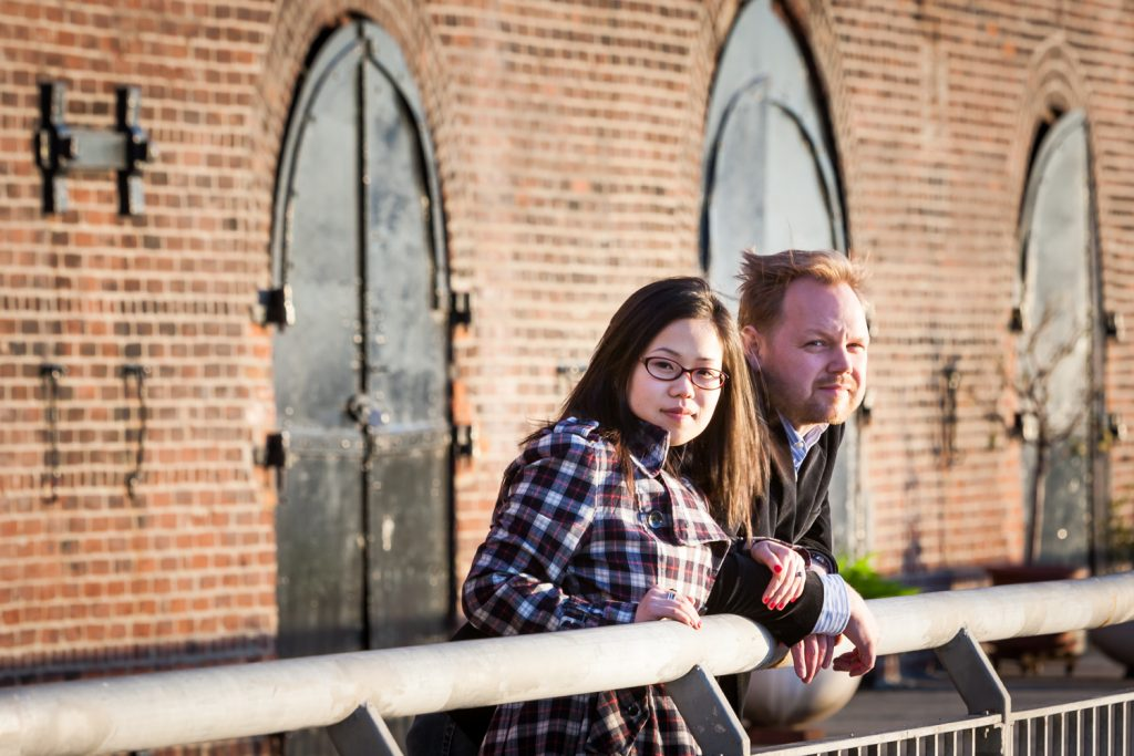 Red Hook engagement photos of couple leaning on railing
