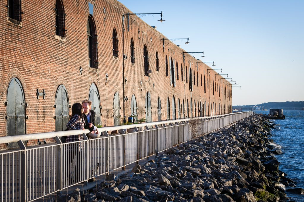 Red Hook engagement photos of couple leaning on railing with brick building in background