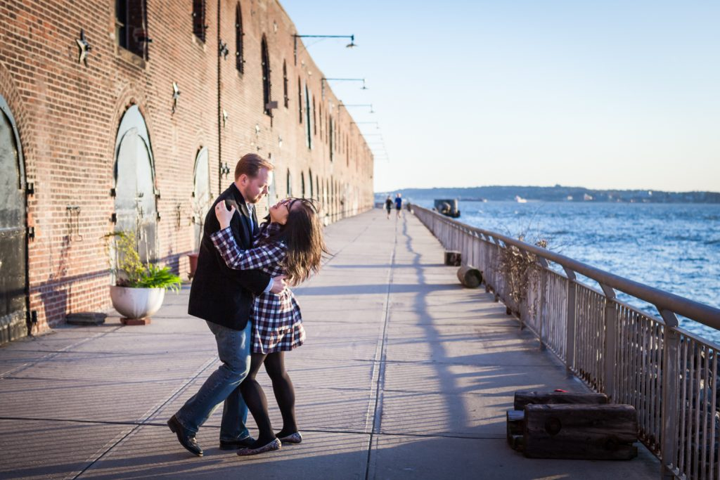 Red Hook engagement photos of couple dancing in front of brick building