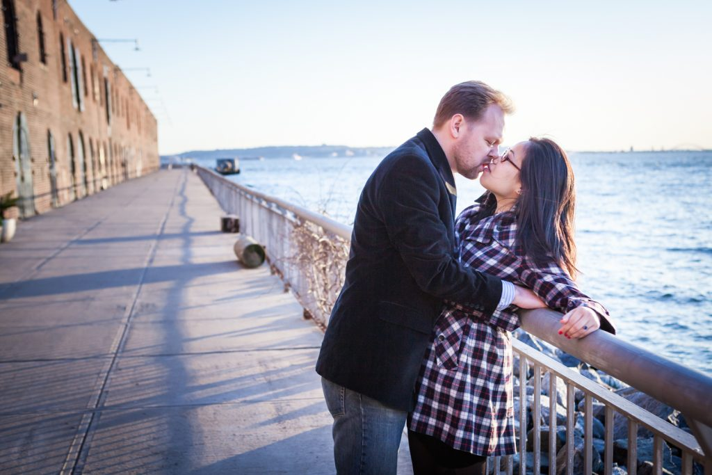 Red Hook engagement photos of couple kissing against railing