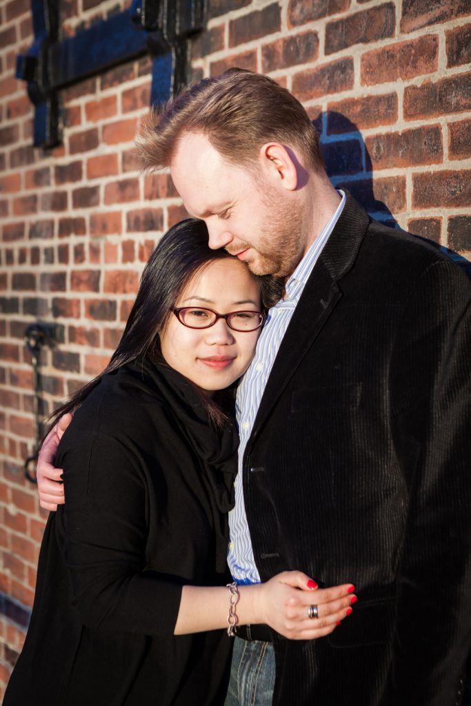 Red Hook engagement photos of couple in front of brick wall