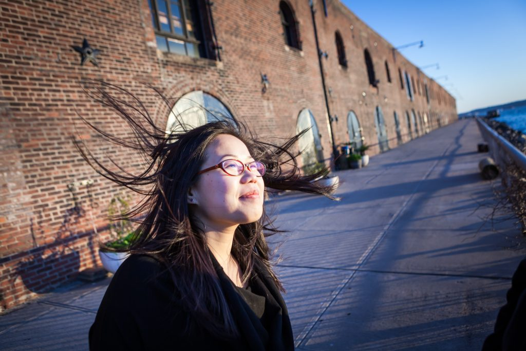 Red Hook engagement photos of woman with hair flying in front of brick building