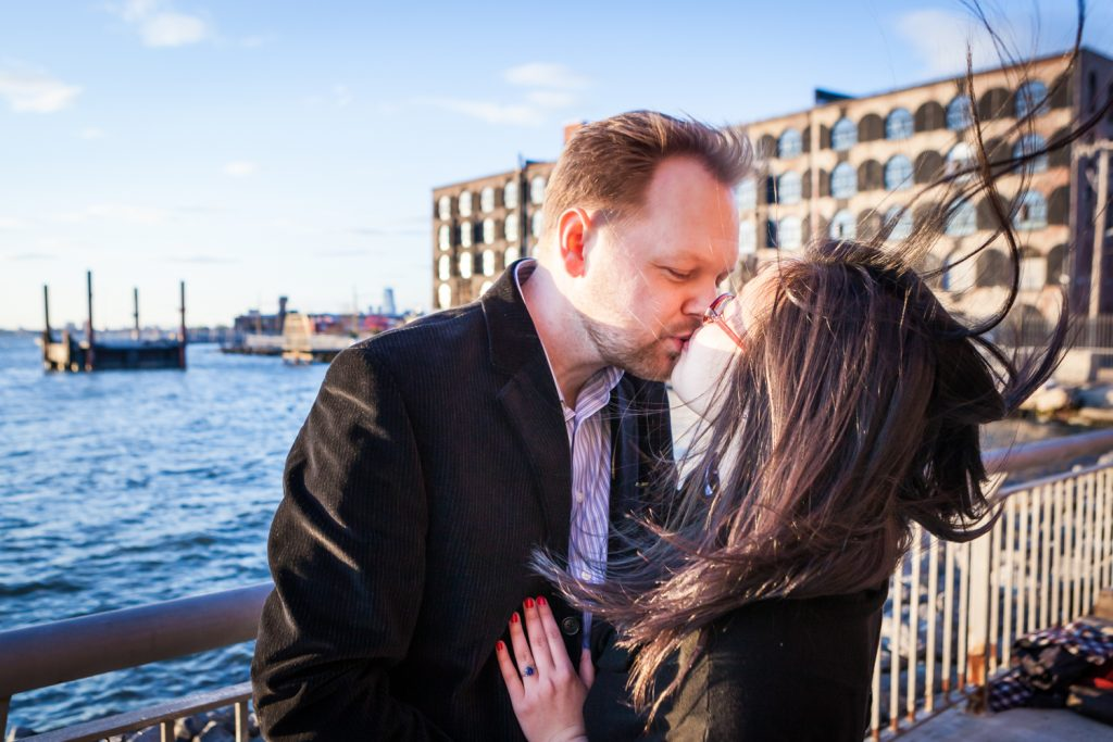 Red Hook engagement photos of couple kissing in front of East River