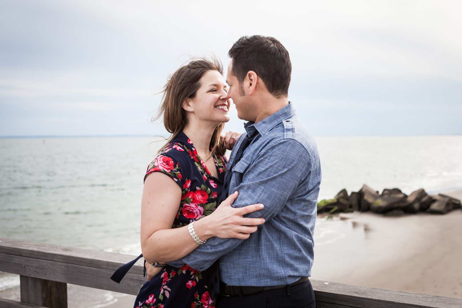 Couple together against pier railing Couple dancing on boardwalk in front of mirror Couple sitting on rock by beach for an article on Coney Island engagement photo tips