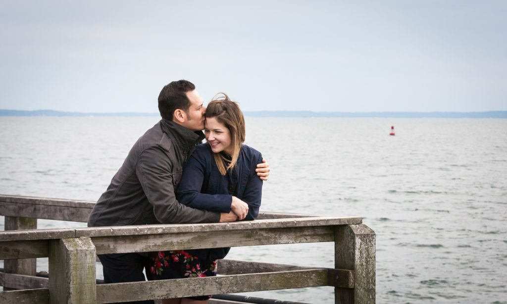 Man kissing woman against railing of pier for an article on Coney Island engagement photo tips
