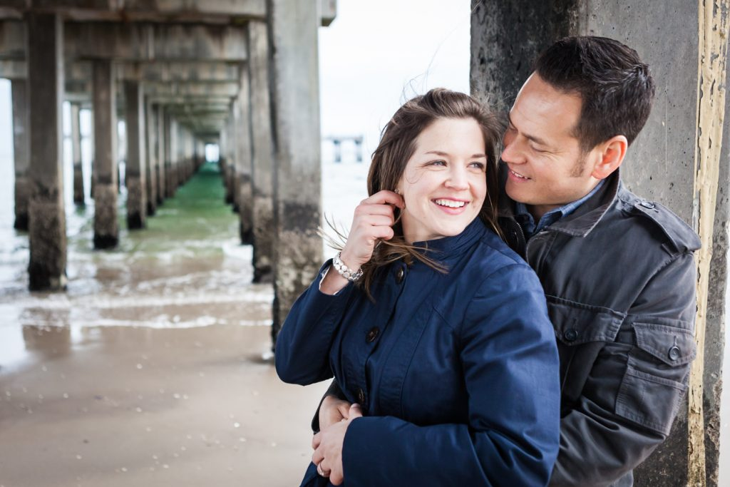 Couple leaning against column under boardwalk for an article on Coney Island engagement photo tips
