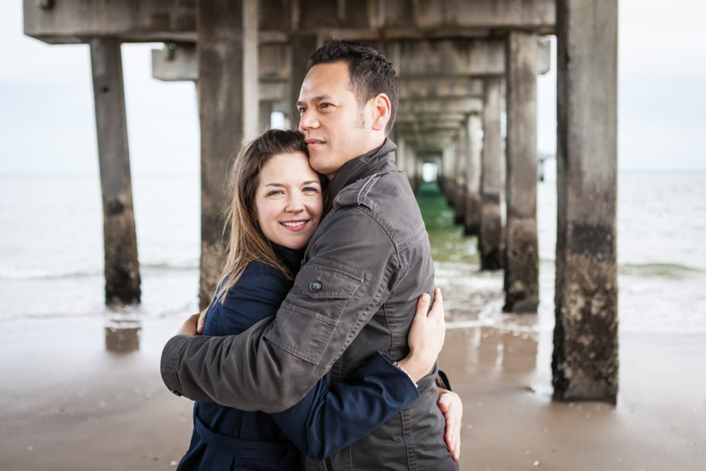 Couple hugging under boardwalk pier for an article on Coney Island engagement photo tips