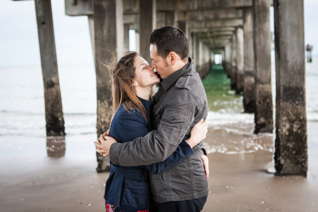 Couple kissing under boardwalk pier for an article on Coney Island engagement photo tips