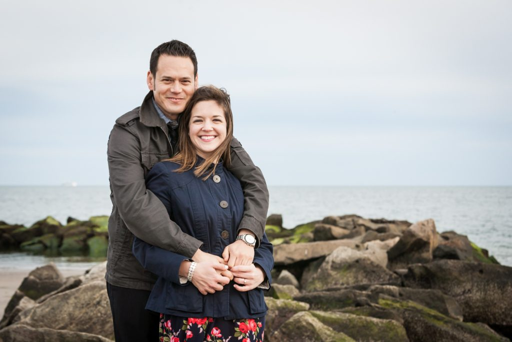 Couple sitting on rock by beach for an article on Coney Island engagement photo tips