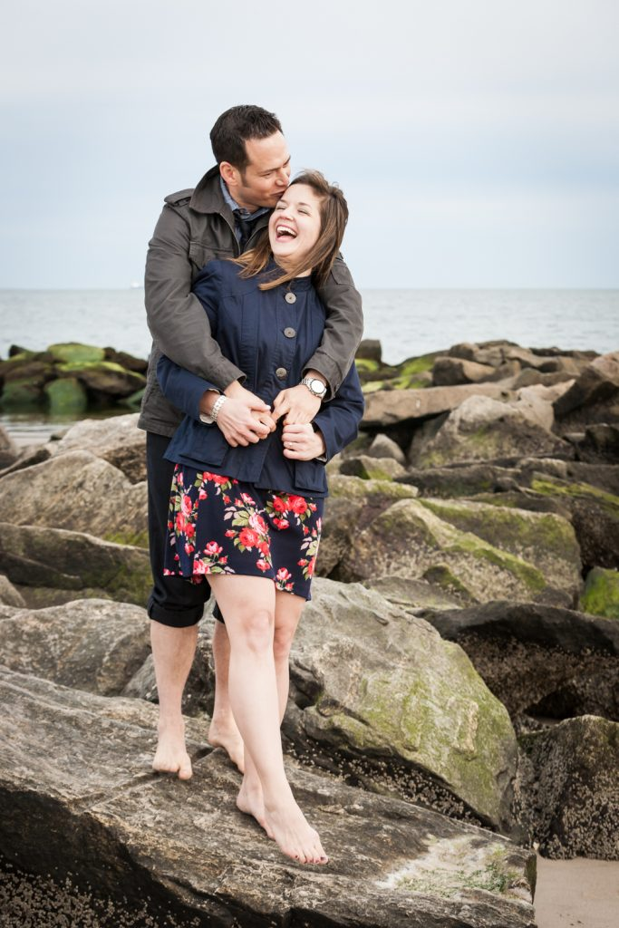 Couple laughing on rock by beach for an article on Coney Island engagement photo tips