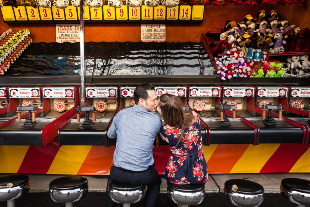 Couple kissing in front of carnival game at Coney Island