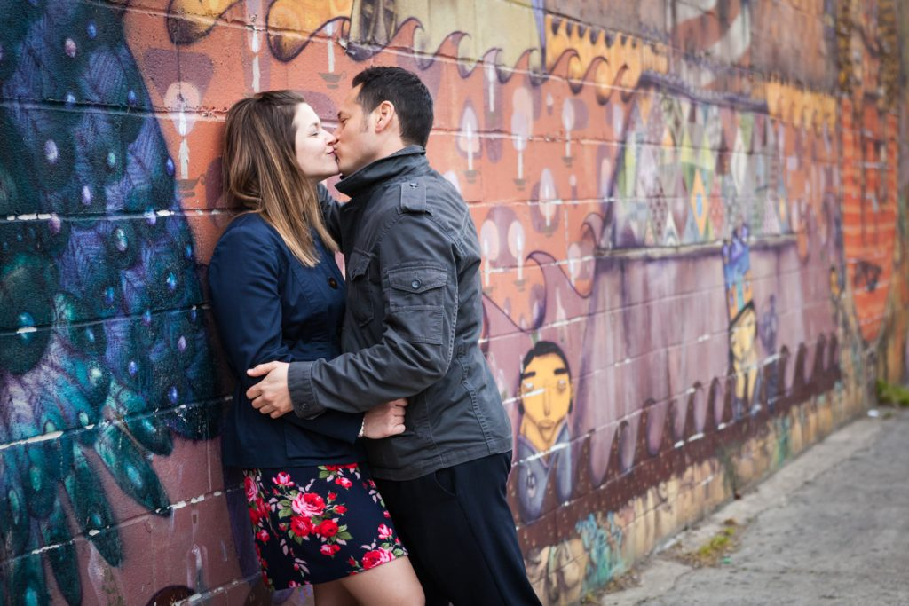 Couple kissing against colorful mural at Coney Island