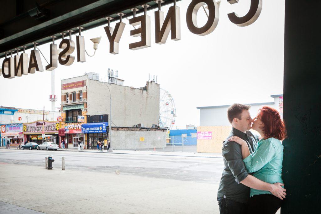 Coney Island engagement photos of couple under neath subway sign