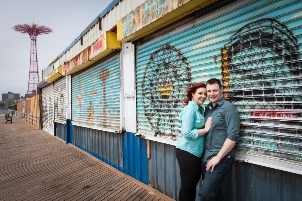 Coney Island engagement photos of couple leaning against colorful metal gate