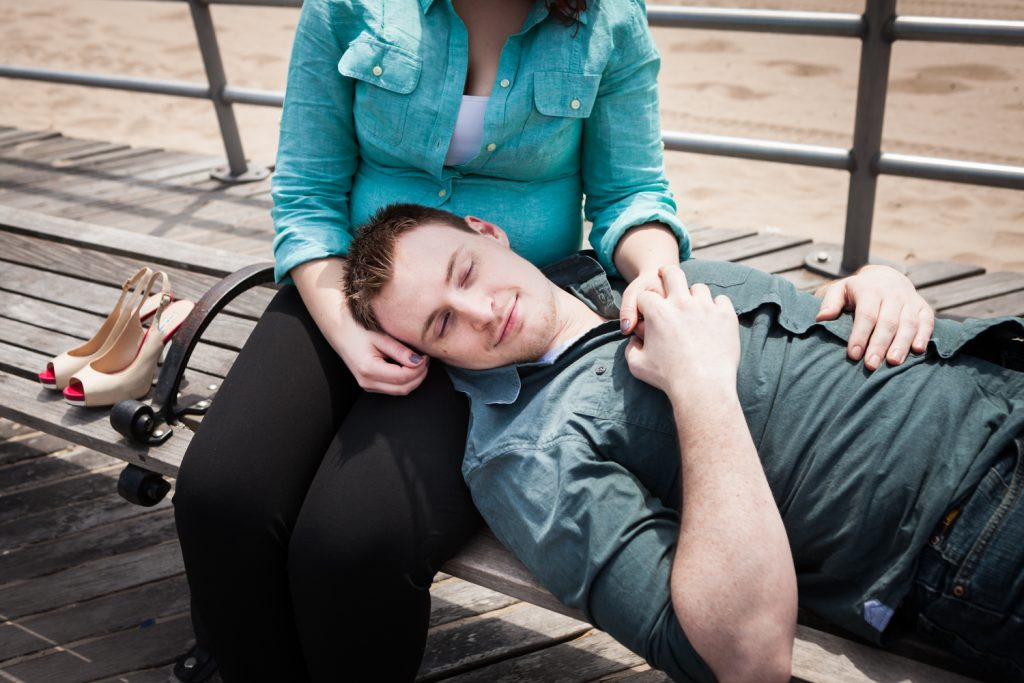 Coney Island engagement photos of man with head in woman's lap on bench