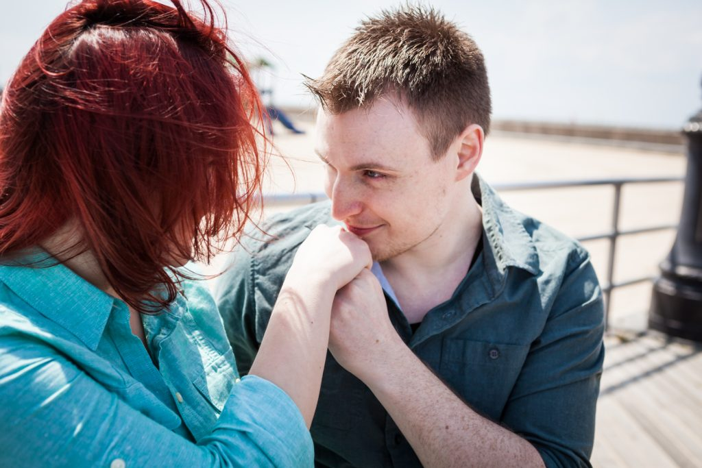 Coney Island engagement photos of man kissing woman's hand