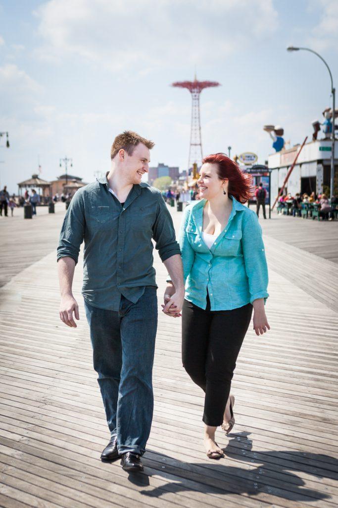 Coney Island engagement photos of couple walking on boardwalk