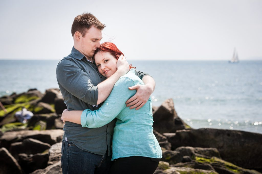 Coney Island engagement photos of couple standing on rock