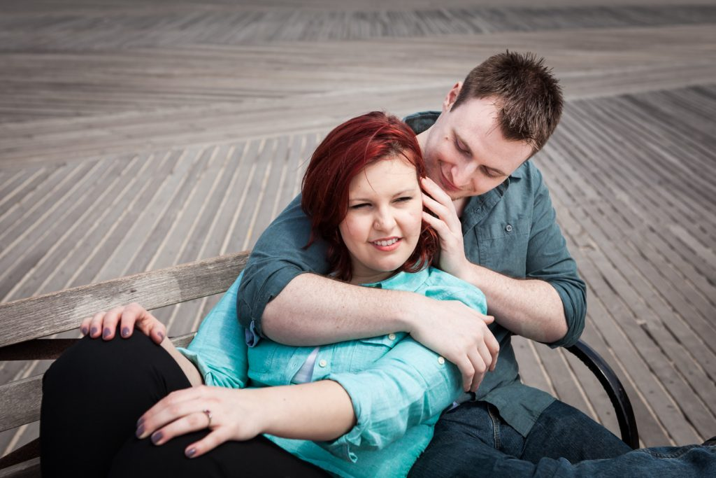 Coney Island engagement photos of woman leaning on man on a bench