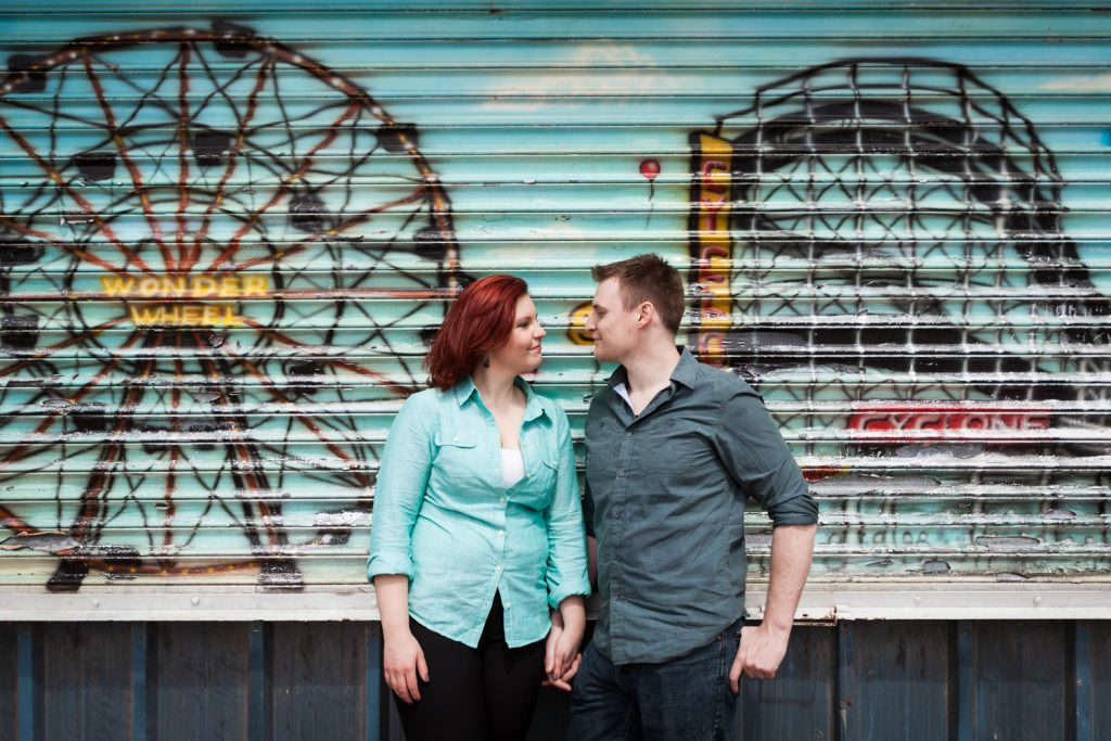 Coney Island engagement photos of couple in front of colorful metal gate